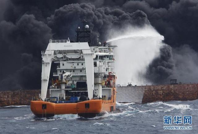"""1月12日,上海海事局的救援船只在向""""桑吉""""轮喷射泡沫降温灭火。交通运输部上海海事局1月12日在上海召开新闻发布会,发布""""桑吉""""轮搜救和污染防控工作的最新进展。记者获悉,目前,""""桑吉""""轮火势较大,不断发生爆燃,具有爆炸和沉没危险。中国救援人员正冒着巨大的生命危险和安全威胁不断接近事故船只,全力做好人员搜救、消防灭火、污染防控工作。新华社发"""