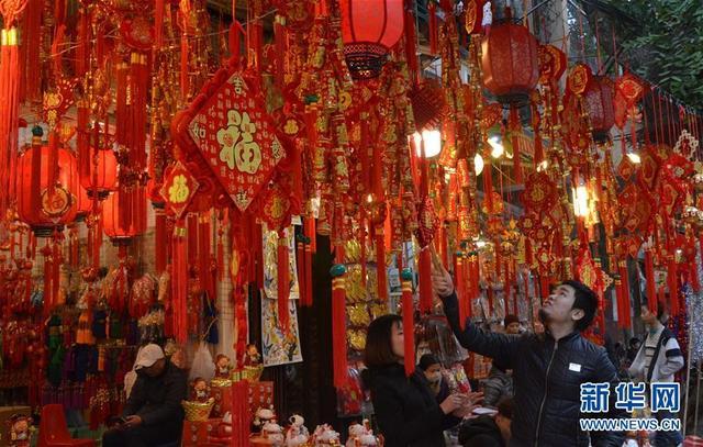 2月12日,在越南首都河内,一名商贩在整理春节装饰品。春节是越南重要的传统节日。临近春节,人们开始采购年货,迎接新春。 新华社记者闫建华摄