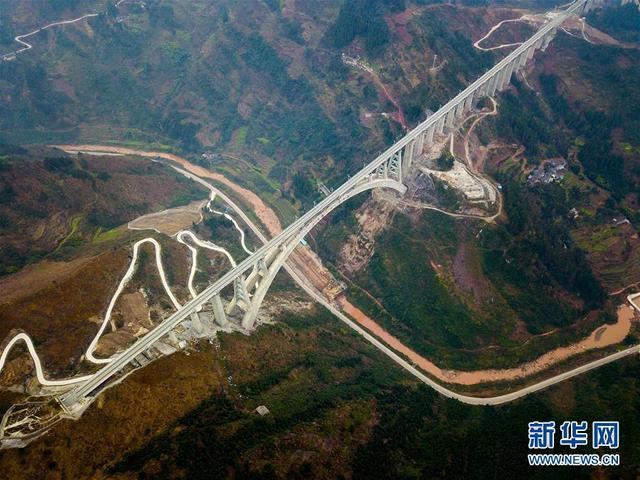 """这是1月11日拍摄的夜郎河大桥。  经过5年多艰苦建设,世界首例""""贯入式大体积嵌岩拱座基础""""大桥——夜郎河特大桥近日落成,与即将开通的渝贵铁路一起进入检测试运行阶段。夜郎河特大桥位于贵州省遵义市桐梓县境内,是渝贵铁路重点控制性工程之一。桥上线路为双线,主桥采用X形""""提篮式""""拱桥设计,最大跨度370米,为国内同类型桥梁跨度第一。  新华社记者 刘潺 摄"""