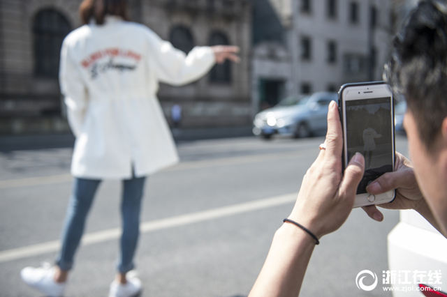 """3月13日,杭城气温飙升,网红街口的淘宝""""试衣间""""又火热开张了。在中山中路一历史建筑前,每天都有几组淘宝模特在此拍照,成为杭州街头一道独特风景。"""