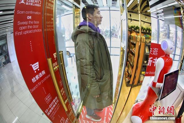 """3月12日,读者在北京""""新华生活+24小时无人智慧书店""""入口处隔间内,脚踩称重感应器,通过人脸识别一体机进入书店。""""新华生活+24小时无人智慧书店""""坐落于北京国际图书城内,占地30平方米,是北京首家24小时无人值守的智慧书店。读者刷脸、扫码、进门、挑选商品、机器人扫码结算、离开,所有环节均无人值守。据该书店负责人穆贝介绍,自1月12日开业以来,目前已接待几百位顾客。2018年,预计将在北京再建20家。大学、写字楼、社区等将成为重点区域。"""