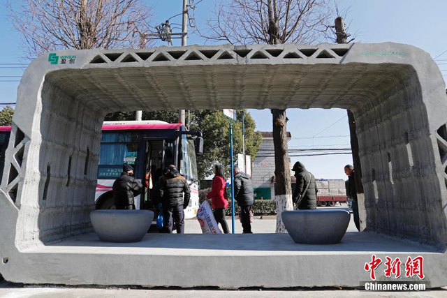 """1月12日,用3D打印方式建造的全球首个公交车站亮相上海,并在枫泾古镇投放使用。这个公交车站跟别的车站都不同,从外观上看,这个车站似乎有点粗糙,在框的表面,还保留着3D打印机器油墨喷嘴打印时的一道道原始""""油墨""""痕迹。 殷立勤 摄"""