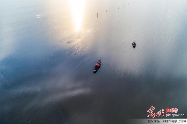 """2018年6月11日,鄱阳湖都昌水域,渔船停靠在云水间。  """"夏秋一水连天,冬春荒滩无边""""是中国最大淡水湖—鄱阳湖独特的自然景观。当日14时,鄱阳湖标志性水文站星子站水位为14.97米,处在丰水期的鄱阳湖开始展现出旖旎的风光。(熊国涛摄/光明图片)"""