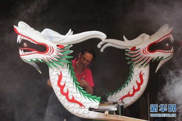 """6月8日,道县龙船头雕刻手艺人陈兵寿在给龙船头裱漆。  端午节临近,湖南省""""龙舟之乡""""永州市道县开始打造一批新龙船,以迎接一年一度的端午节民间龙船大赛。每年的这个时候,也是道县龙船头雕刻手艺人最忙碌的时候。今年56岁的陈兵寿从事龙船头雕刻行当已近40年。据陈兵寿介绍,龙船头采用轻且硬的水柳树为材料,制作工序复杂,有砍料、出胚、粗模合成、雕琢打磨、裱漆等工序。一个龙船头中间镂空,重约30斤,一般需要一个工匠花费12天左右的时间打造而成。道县龙船头雕刻精美、栩栩如生、独具特色。每年端午期间,道县上百条龙船展开竞渡,热闹非凡。  道县龙船赛传承有上千年历史,2006年""""道州龙船赛""""被列入湖南省非物质文化遗产名录。新华社发(何红福 摄)"""