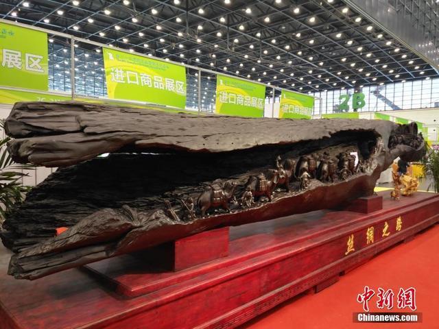 10月12日,一件长达10米、重达10吨的乌木(阴沉木)雕刻作品《丝绸之路》亮相郑州全国商品交易会。据商家介绍,此木源于四川雅安,耗时两年手工雕琢而成。记者看到,木心内雕有丝路盛景,古代商贾在大漠中牵着载货骆驼,砥砺前行,上方还雕有多尊佛像。此景寓意中国商人走向世界。商家给出的参考价是9999万元。董飞 摄