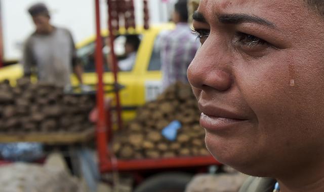 """当地时间2019年2月9日,哥伦比亚库库塔,与委内瑞拉塔奇拉接壤的西蒙玻利瓦尔国际大桥上,一名委内瑞拉女子接受采访。由于国内物资短缺,委内瑞拉人通过该桥到哥伦比亚购买日用品。委内瑞拉总统马杜罗8日誓言不会让反对派领导人瓜伊多要求的美国""""虚假""""援助进入委内瑞拉。"""