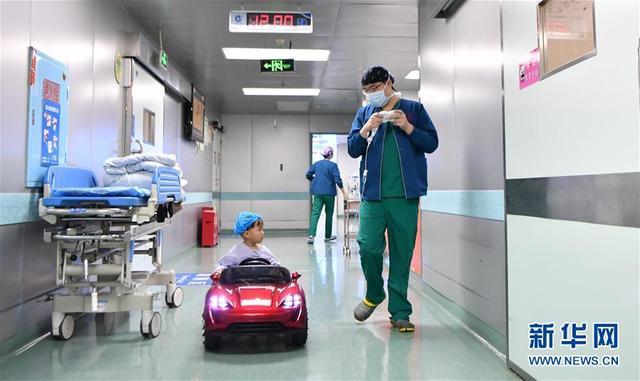 """1月11日,希希(化名)开着玩具汽车前往手术室。自2017年10月起,湖南省儿童医院实行新举措:让接受手术的孩子们""""开着汽车""""进入手术室,以稳定患儿情绪、保障麻醉安全。从新举措实施以来,儿童医院已有100多位1至6岁的患者享受了""""汽车服务""""。新华社发(薛宇舸 摄)"""