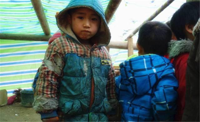 """近日云南""""冰花男孩""""走红,引起了网友共鸣,在公益摄影师镜头里记录了很多类似的留守儿童,他们用自己单薄的身体抵御严寒。2016年志愿者走访广西南丹县,小男孩为了御寒,用一根绿色的绳子扎紧了已经破烂不堪的棉衣,整个身体冻得哆嗦。(摄影 张羽锋)"""