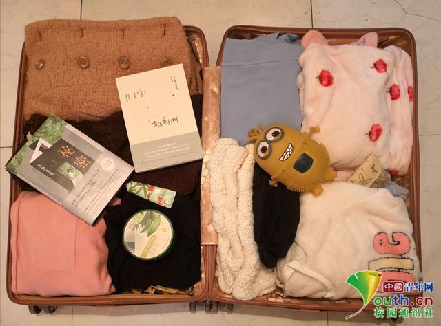 """辽宁师范大学学生刘桂芳的春节行李箱里大多是衣物,她说,因为离家太远,要转多次车,箱子太重不好带回家。""""因为喜欢看书,所以带了两本喜欢的,想着在家也不能落下读书。护手霜和芦荟胶必须带着,我家这边冷怕冻伤。小黄人是朋友送的礼物,要带回家好好珍藏啦。""""本人供图"""