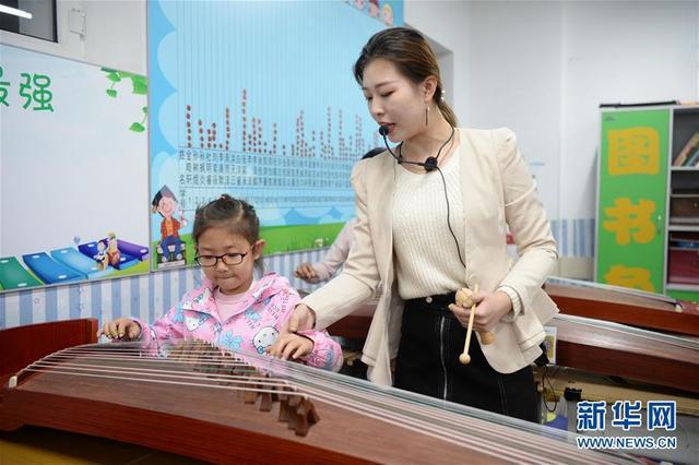 10月10日,哈尔滨市铁岭小学老师(右)在校内课后服务课堂上指导学生弹奏古筝。 新华社记者 王凯 摄