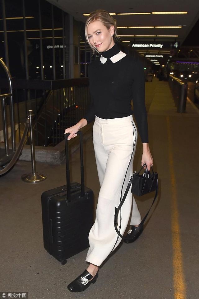 新浪娱乐讯 11日,洛杉矶,超模卡莉·克劳斯(Karlie Kloss)亮相机场,她身穿黑色毛衣搭配白色阔腿裤,穿搭做减法展现高级美。