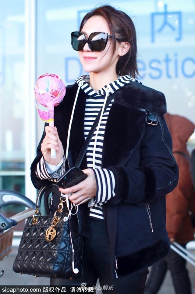 新浪娱乐讯 2月11日,黄梦莹现身北京机场。她穿黑色外套搭配黑白条纹卫衣,戴着墨镜潮范儿十足,手里却拿着粉色超大棒棒糖,推车里还放着小猪佩奇,反差萌显得十分可爱。(sipa/图)