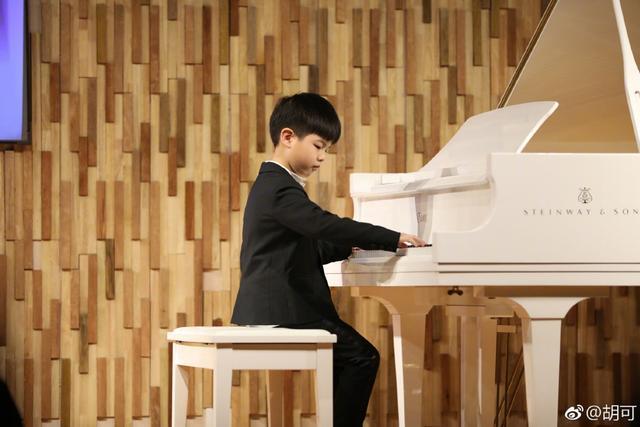 新浪娱乐讯 1月12日,演员胡可在微博分享儿子安吉的近照,照片中安吉身穿黑色西装搭配白衬衫,端坐在一架白色钢琴边认真演奏,帅气又儒雅。