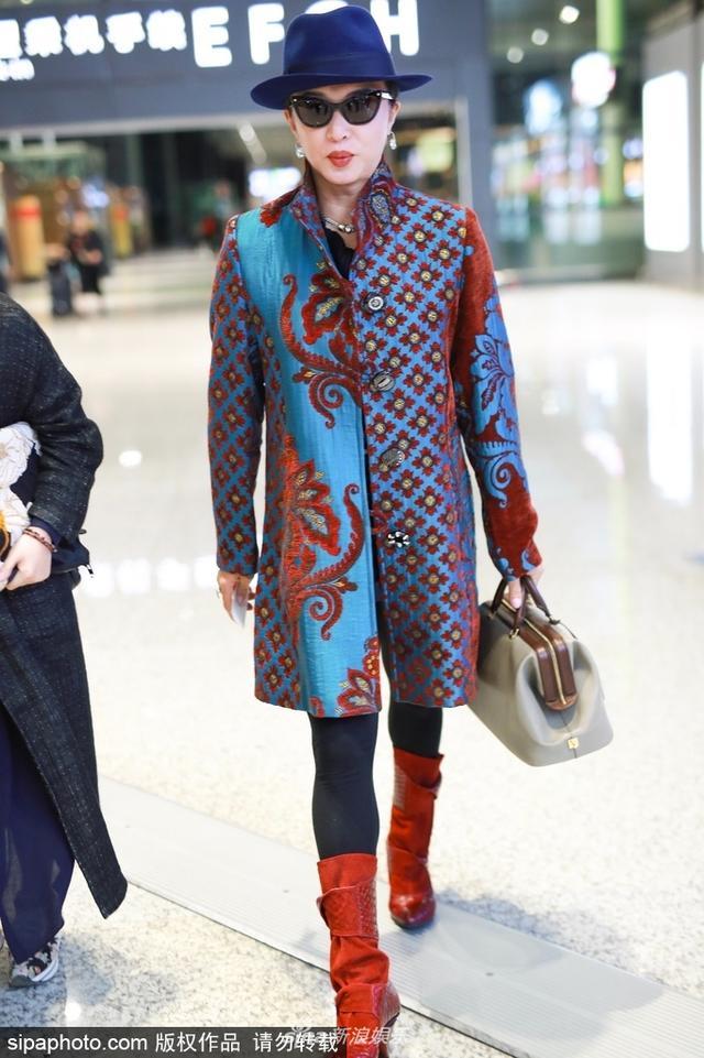 新浪娱乐讯 2018年10月11日,上海,金星现身机场。金星戴礼帽穿刺绣外套,她踩长靴,似穿越成上海滩女特工,对镜头挥手气场冲天。(SIPA/图)