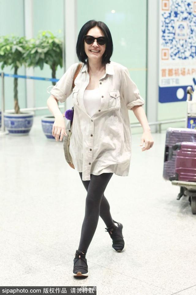 """新浪娱乐讯 2018年7月11日讯,北京,近日,小S徐熙娣现身机场。她看到镜头立刻""""戏精""""附体,先是揽着助理的胳膊狂摆pose,随后又在机场跳起""""太空步""""。(SIPA/图)"""