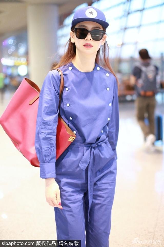 新浪娱乐讯 日前,戚薇从北京机场飞往上海机场。她身穿工装连体裤,搭配红唇红手机红包包,时尚有型。SIPA/图