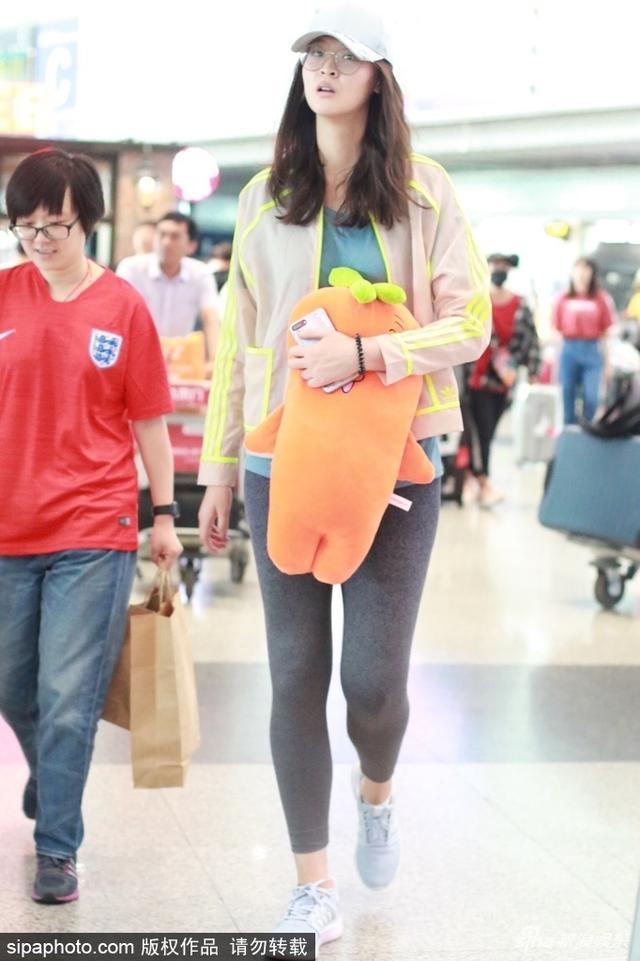 """新浪娱乐讯 日前,惠若琪现身机场。她穿着蓝色T恤、灰色运动裤和运动外套,戴着眼镜和棒球帽,怀里紧紧抱着""""萝卜""""玩偶,低头似在犯困。SIPA/图"""