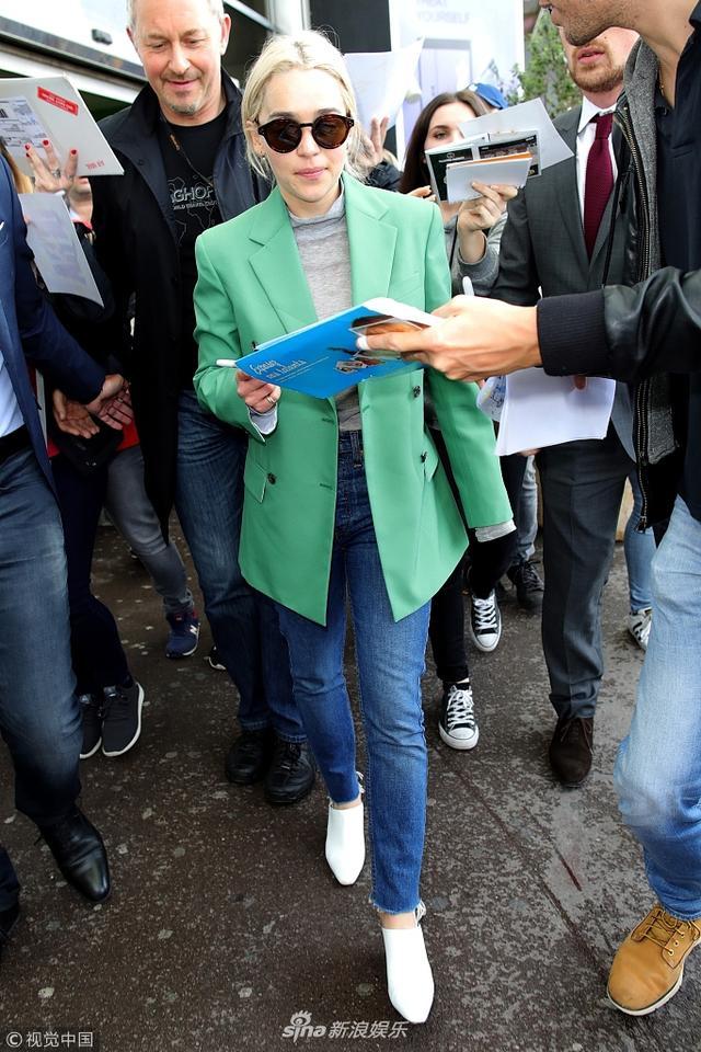 """新浪娱乐讯 日前,""""龙母""""艾米莉亚·克拉克(Emilia Clarke)抵达尼斯机场。艾米莉亚·克拉克绿色西装配牛仔裤,清爽又帅气,遭粉丝围堵身材显娇小。视觉中国/图"""