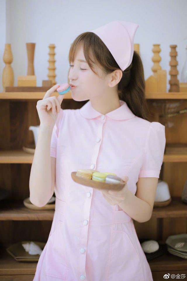 新浪娱乐讯 10月11日,金莎晒出自己的粉色护士服造型,图中她清纯可爱,嘟唇亲吻小点心甜笑动人。