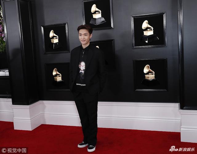 新浪娱乐讯 当地时间2019年2月10日,第61届格莱美颁奖礼在洛杉矶举行,现场星光璀璨,张艺兴一身黑色西服装扮亮相红毯,他露出酒窝冲镜头甜笑,双手比赞帅气绅士。(视觉中国/摄影)
