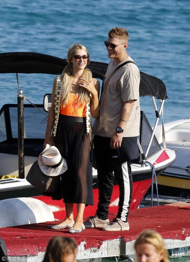 """新浪娱乐讯 当地时间2018年7月10日,帕丽斯·希尔顿(Paris Hilton)和未婚夫克里斯·泽尔卡(Chris Zylka)度假。希尔顿穿着橙色泳衣和黑色纱裙,梳着双马尾变""""村花"""",从身后搂住未婚夫cosplay《泰坦尼克号》经典场景。(视觉中国/图)"""
