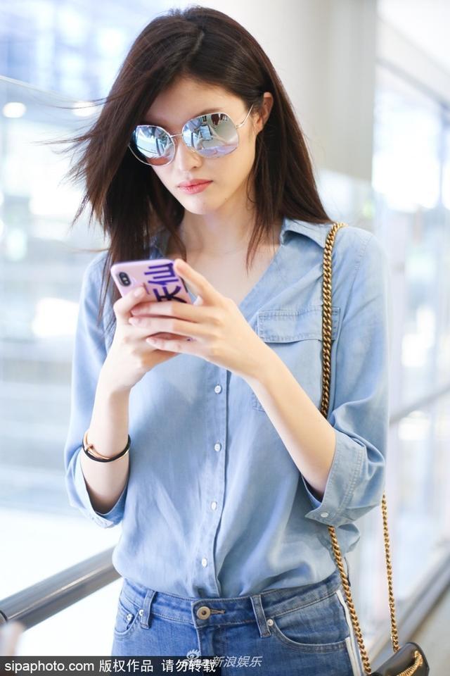"""新浪娱乐讯  2018年6月14日,超模何穗现身上海机场,她手拿手机不停刷,粉色的手机壳上写着""""美若天仙"""",真是相当自信,她一头黑长直非常飘逸,冲着镜头露酒窝甜笑。(图文:sipa)"""