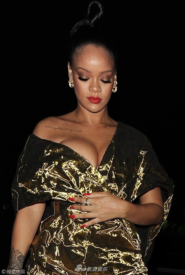 """新浪娱乐讯  伦敦当地时间2018年6月13日,蕾哈娜(Rihanna)现身电影《瞒天过海:美人计》( Ocean's Eight)首映派对。蕾哈娜似裹金黄色""""糖纸"""",在黑夜中依然熠熠生辉。蕾哈娜手捂肚子低头疾走,大秀傲人酥胸露事业线。(图文:视觉中国)"""
