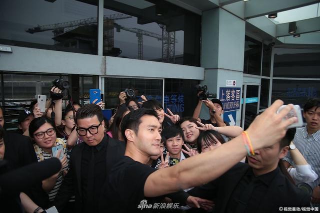 """新浪娱乐讯  2018年6月14日,香港,崔始源抵达机场。穿一身黑衣的他遇无数迷妹接机,人气超高,获保镖层层保护,仍然努力突出""""重围""""与粉丝合影,超暖心。(图文:tungstar)"""