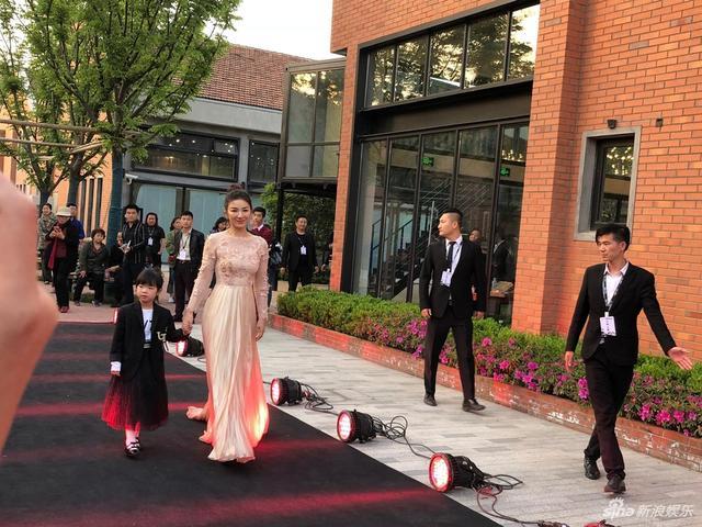 """新浪娱乐讯 近日,黄奕带5岁女儿""""铛铛""""黄芊玲参加了在北京举行的时装秀,黄奕一身金色礼服轻盈如少女,女儿则身穿黑色小西装搭配小纱裙,越发长得俏皮可爱,铛铛还和模特一起走了T台,小小年纪,台风很稳。"""