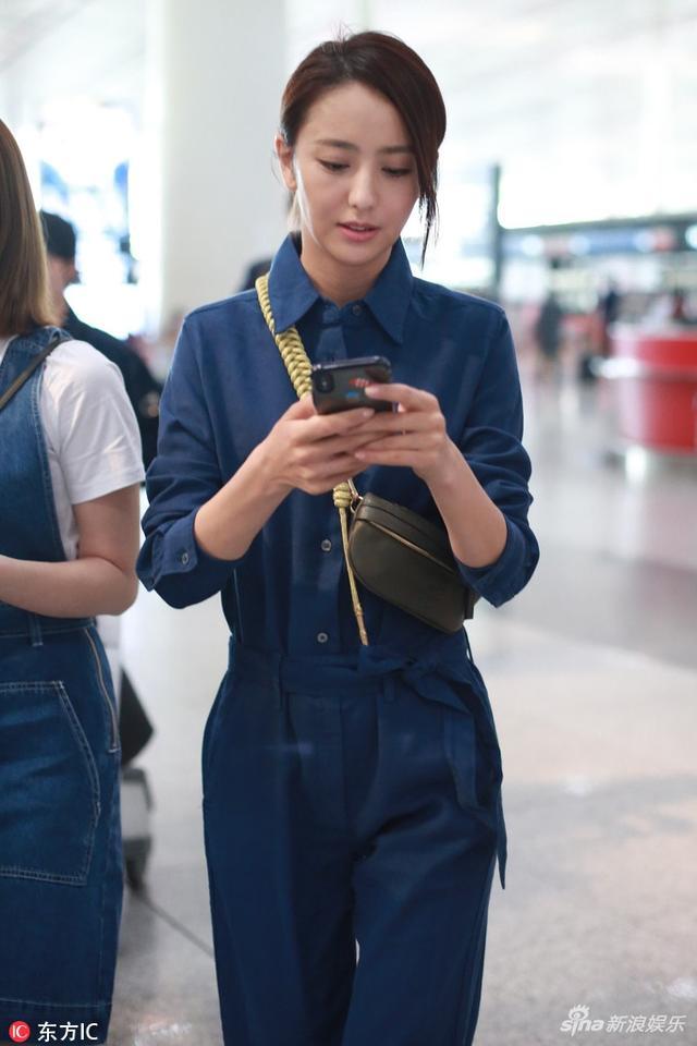 新浪娱乐讯 佟丽娅近日现身机场,深蓝色连衣裤显干练十足,只见她一路忙回手机消息变身低头一族。IC/图