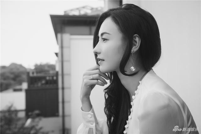 """近日,张柏芝曝光了一组片场随手拍照片。只见她身着一袭缎面白裙,黑色长发飘逸动人,站在阳台上眺望远方,眼神温婉动人。尤其让人注意的是,她还搭配了若隐若现的珍珠长款耳饰,与简约别致的戒指遥相呼应,尽显复古优雅气质。虽然是随手拍的照片,但在黑白光影的下,张柏芝精致的五官还展现了令人惊艳的""""侧颜杀"""",让网友大呼:""""这位小姐姐实在是太美了!"""""""