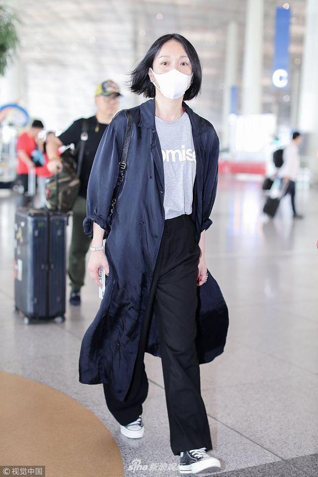 新浪娱乐讯 2018年5月15日,北京,周迅现身机场,她身穿蓝色风衣搭配T恤阔腿裤造型十分休闲,素颜遮口罩走路带风气场满满,小短发彰显清新气质。(视觉中国/图)