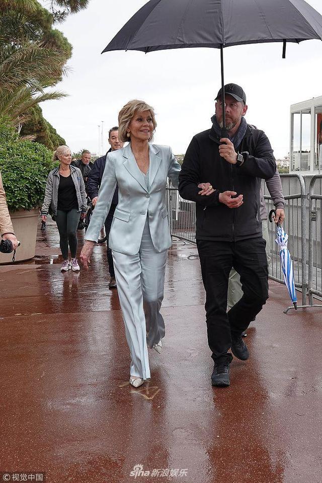 """新浪娱乐讯 当地时间2018年5月14日,法国戛纳,第71届戛纳国际电影节,  """"老牌影后""""简·方达(Jane Fonda)现身街头。81岁的简·方达身穿天蓝色套装走路带风,紧握保镖撑伞亮相,气场似女王。(视觉中国/图)"""