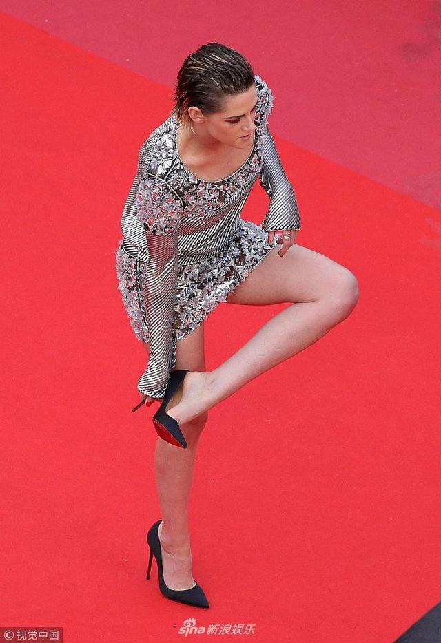 """新浪娱乐讯 当地时间2018年5月12日,法国戛纳,第71届戛纳国际电影节,主竞赛单元《黑色党徒》(Blackkklansman)举办首映礼。 """"暮光女""""克里斯汀·斯图尔特(Kristen Stewart)遇上下雨,直接脱掉高跟鞋赤脚走红毯,超级率性。(视觉中国/图)"""