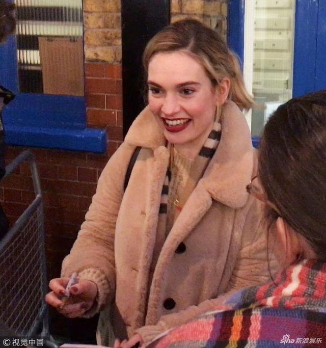 新浪娱乐讯 当地时间2019年3月14日,伦敦,莉莉·詹姆斯(Lily James)离开剧院。表演结束后她笑容满面,亲切为粉丝签名。(视觉中国/图)