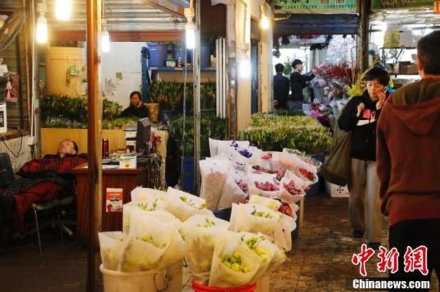 11月13日,民众在上海万航渡路33号的曹家渡花鸟市场里购买鲜花,但生意清淡了很多,商铺纷纷打出了清仓特价的广告。