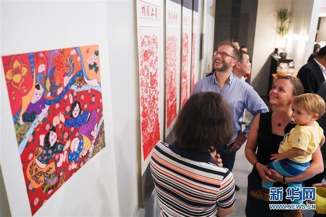 """8月29日,观众在比利时布鲁塞尔中欧文化之家观看河北省民间美术作品展。当日,""""沃野之上——河北省民间美术作品展""""在比利时布鲁塞尔中欧文化之家举行。展览展出来自河北省的辛集农民画和丰宁剪纸,吸引了众多观众。新华社记者郑焕松摄"""