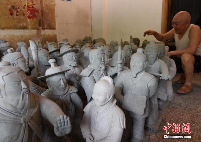 7月10日,73岁的牟登德在重庆家中展示自己的石刻作品。只有小学文化的他从影视剧和小人书中汲取灵感加上石匠技艺,在近50年时间里,雕刻出四大名著中的经典人物。中新社记者 周毅 摄