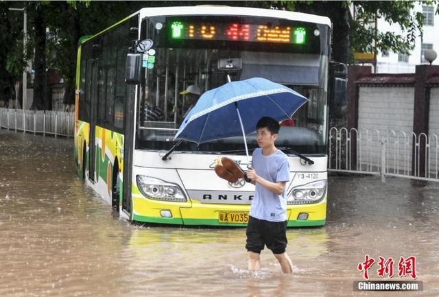 """6月8日,广州天河区员村二横路,一名男子""""踏浪""""出行。当日,受台风""""艾云尼""""影响,广州市区出现暴雨到大暴雨,全市共有86个测站雨量超过100毫米,最大累积降水量出现在南沙区新兴村,为172.5毫米。 中新社记者 陈骥旻 摄"""