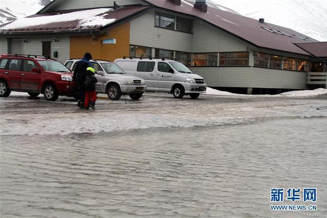 """就在欧洲大部分地区突遇寒冬之际,全球最北小镇朗伊尔城却经历异乎寻常的北极""""高温""""天气。图为2月27日,在挪威朗伊尔城,两名行人走过冰雪融化的路面。 新华社记者 梁有昶 摄 图片来源:新华网"""