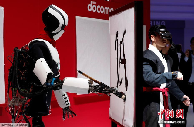 """当地时间2018年2月28日,西班牙巴塞罗那,""""5G机器人""""利用5G技术实现与操控者同步动作,完成书法写作,并可以跟随工作人员做相同的模仿动作。"""