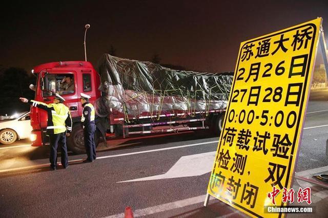 """2月27日凌晨,苏通长江公路大桥通车10年首次荷载试验检测进入第二天,民警在收费站封闭现场忙碌。通车近10年的苏通大桥迎来首次夜间全封闭式""""体检"""",工作人员利用2月26、27、28日三天的0:00至5:00进行荷载试验,期间大桥双向交通管制。许丛军 摄"""