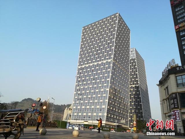 """钢筋水泥筑成的大楼都是笔直方正,而在重庆两栋百米高的大楼竟然是倾斜的,像是快要""""倾倒"""",被人们称为""""歪歪楼""""。然而这并不是视觉上的错觉,这两栋大楼是真的""""倾斜""""!不明所以的人路过看到不禁两腿发颤,赶紧躲开。 贾楠 摄"""