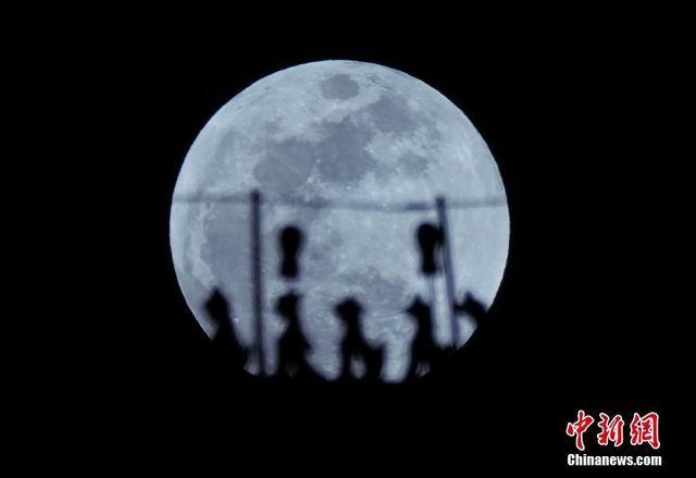 """1月31日,一场罕见的""""三月合一""""在北京上空出现。中新社记者 毛建军 摄"""