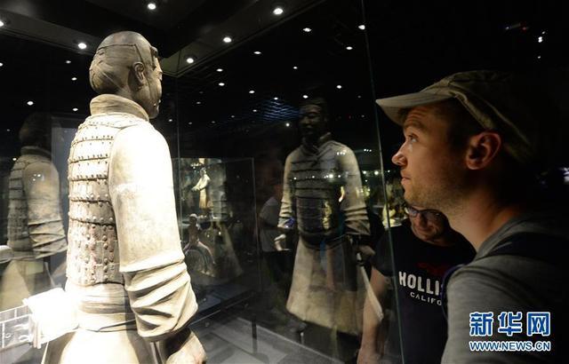 一位外国游客在参观展出的秦骑兵俑。
