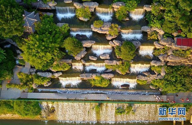 7月29日,市民在广西柳州市窑埠古镇人工瀑布群下消暑纳凉(无人机拍摄)。    炎炎夏日,柳州市区柳江沿岸的人工瀑布群每天定时开放,为市民送去清凉。    新华社发(黎寒池 摄)