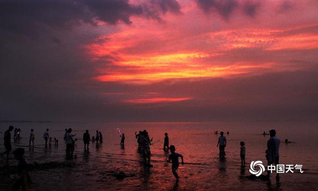 中国天气网广西站讯 8月9日,北海天气依旧炎热,傍晚时分暑热微减,许多市民和游客选择北岸的沙滩作为饭后休闲的去处。人们在放松心境的同时,也欣赏着姹紫嫣红的美丽晚霞。(图/卢威旭 文/何启玄)
