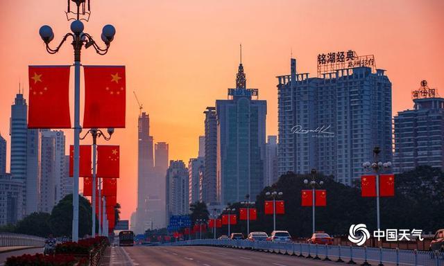 中国天气广西站讯 10月1日,我们迎来了新中国69岁华诞,南宁清晨太阳升起,金灿灿的阳光洒在民族大道上,悬挂着的五星红旗,一面面排成行迎风招展,在车流、高楼的映衬下格外美丽,前来游玩的市民都都感受到了国庆的喜庆。(文/赖雨薇 图/王晋)