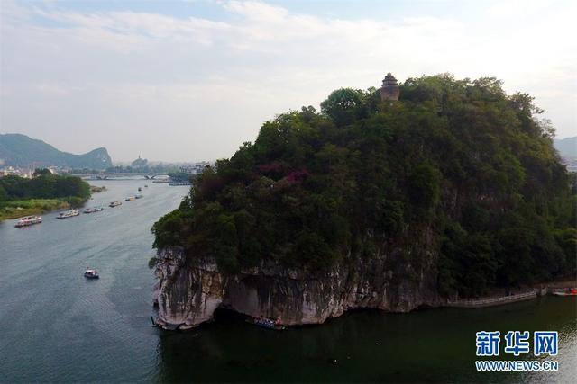 """漓江是桂林的标志水,象鼻山则是桂林的标志山,也是桂林市的城徽。象鼻山坐落于漓江与桃花江汇流处,其山形酷似一头驻足漓江边临流饮水的大象。山体前部的水月洞,弯如满月,清碧的江水从洞中穿鼻而过,波光洞影,构成""""水底有明月,水上明月浮""""的奇观,""""象山水月""""因而成为桂林山水一绝。新华网发 韦秀玲 摄"""