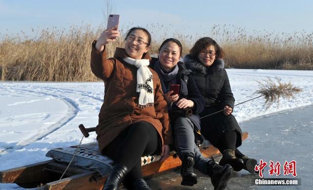 """1月30日,河北雄安新区白洋淀湖面结了厚厚的冰,民众在此冰钓、滑冰,这里俨然成了一个天然的""""游乐场""""。图为到白洋淀游玩的民众合影留念。中新社记者 韩冰 摄"""